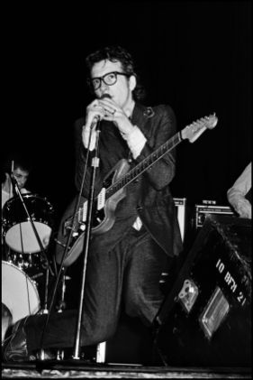 Elvis Costello drops to his knees during Watching the Detectives