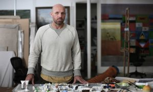 """The Guardian, 16 May 2015. """"Stroke of genius: Peter Doig's eerie art whisks the mind to enchanted places."""" Peter Doig in his London studio. Photograph: Martin Godwin."""
