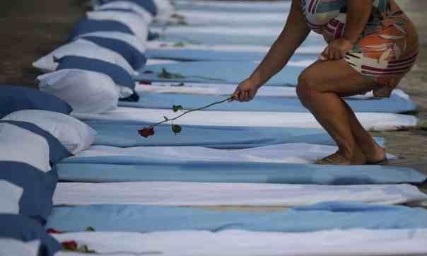 A woman lays a rose on mattresses symbolising coronavirus victims, at a protest in Rio against Bolsonaro's pandemic response. Photograph: Carl de Souza/AFP/Getty Images