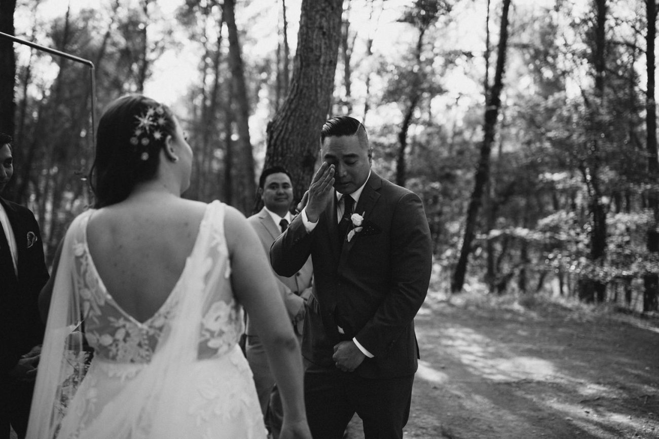 Emotional groom after seeing bride for the first time during outdoor forest ceremony