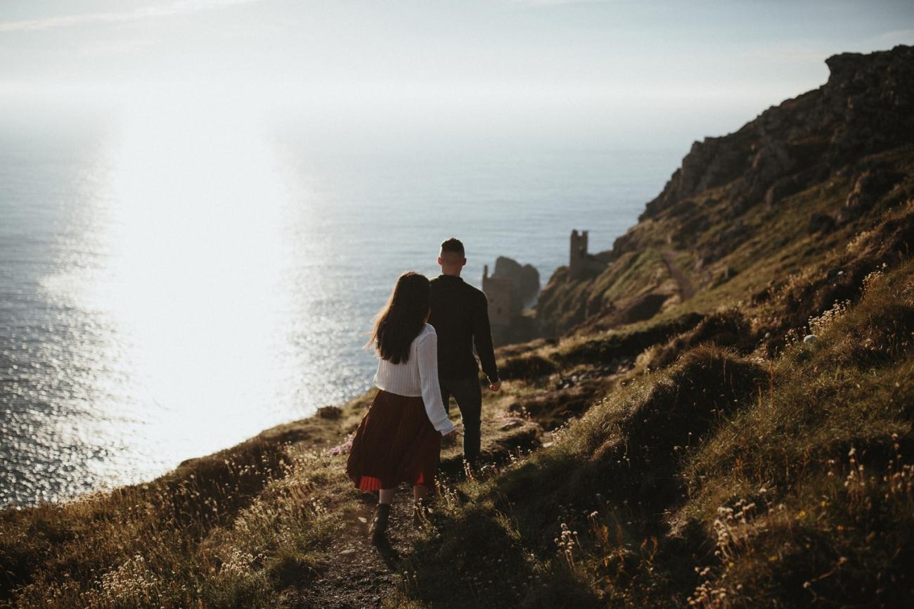 Couple walking together along the Cornish coastline