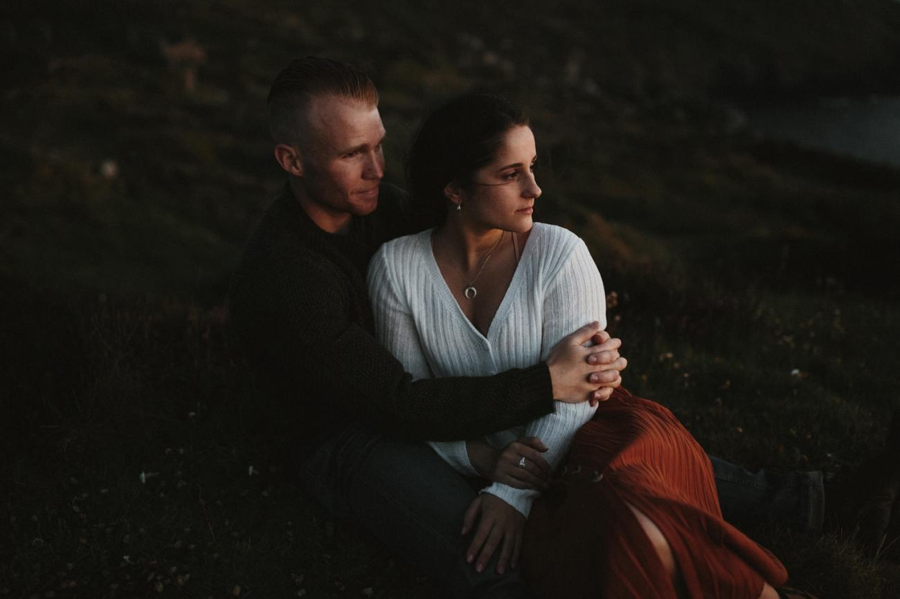 Couple hugging each other on the grassy hill during their Cornwall Engagement session
