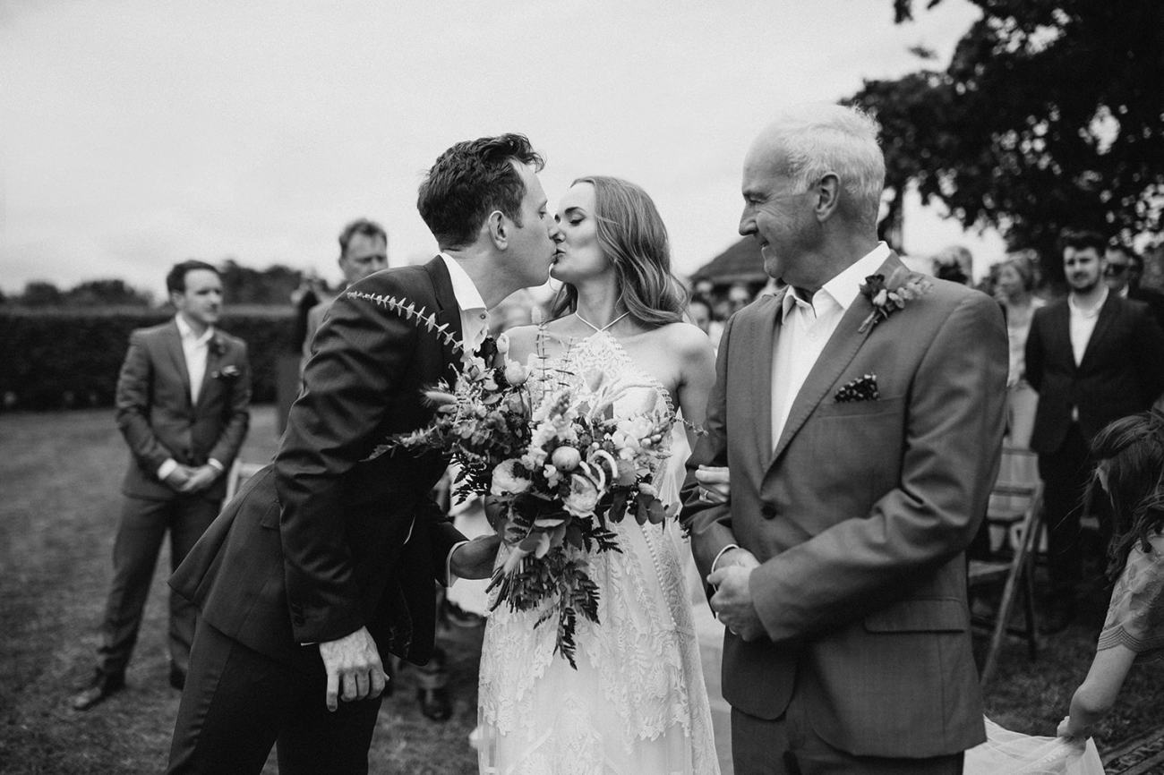 Groom kissing bride during outdoor wedding in essex