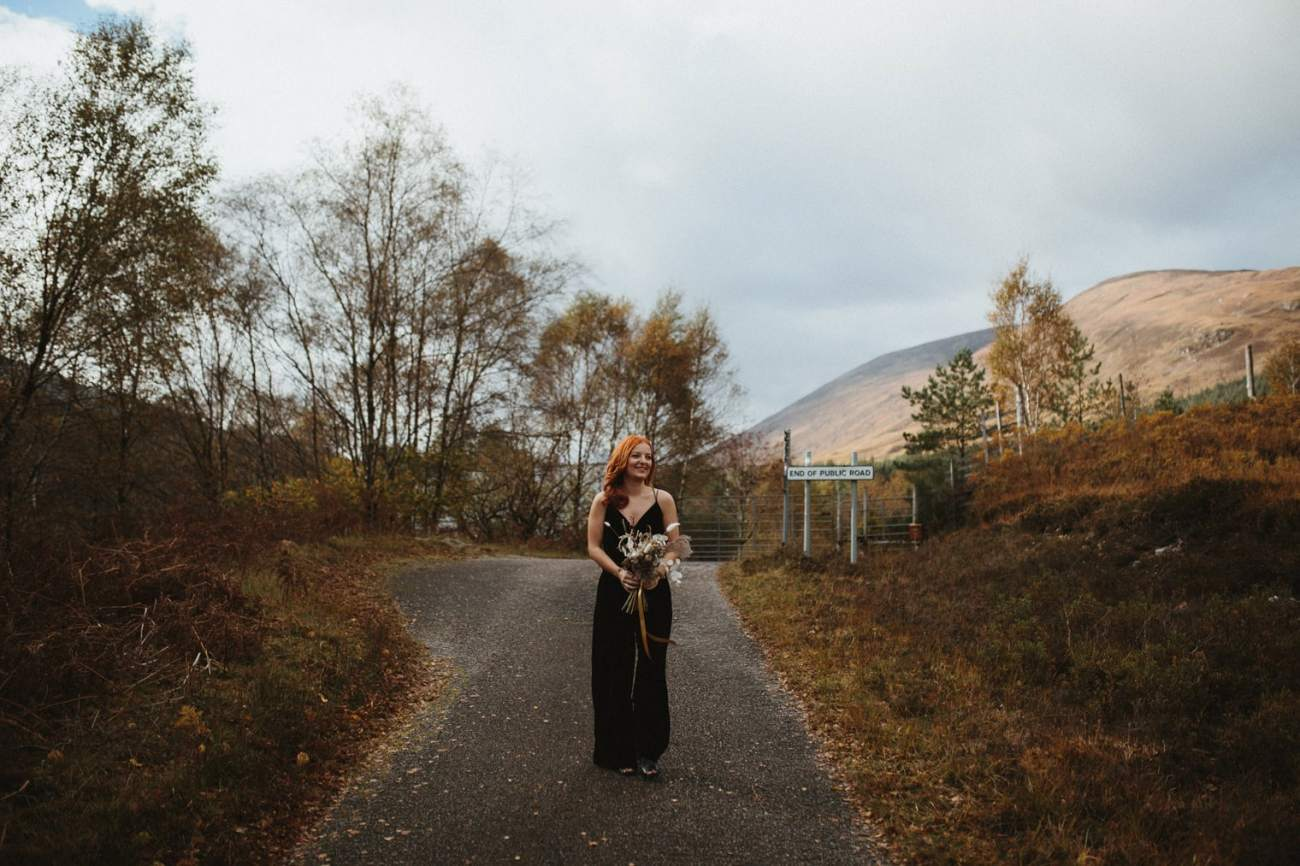 bride wearing black velvet jumpsuit walking to greet groom for first look