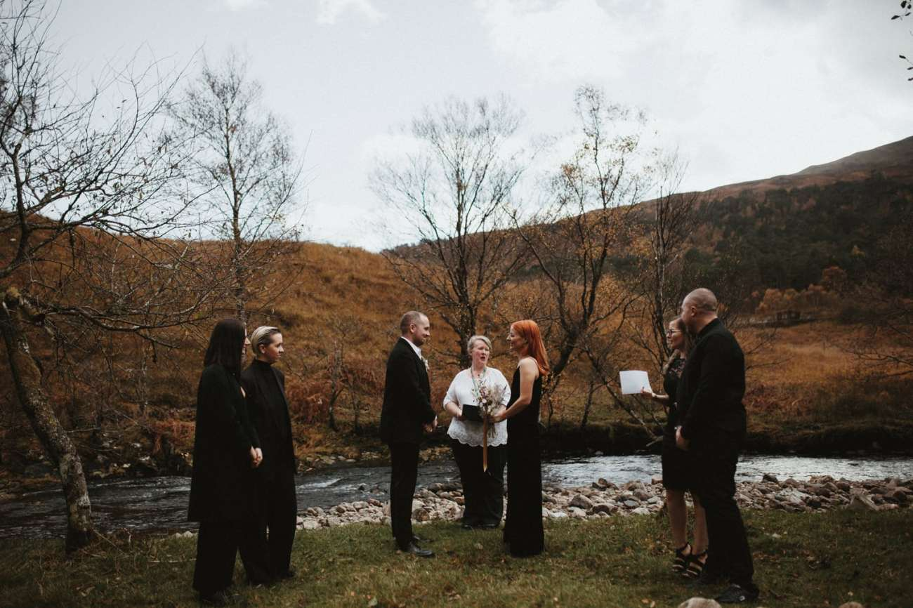 intimate wedding ceremony being held during autumn elopement in the scottish highlands