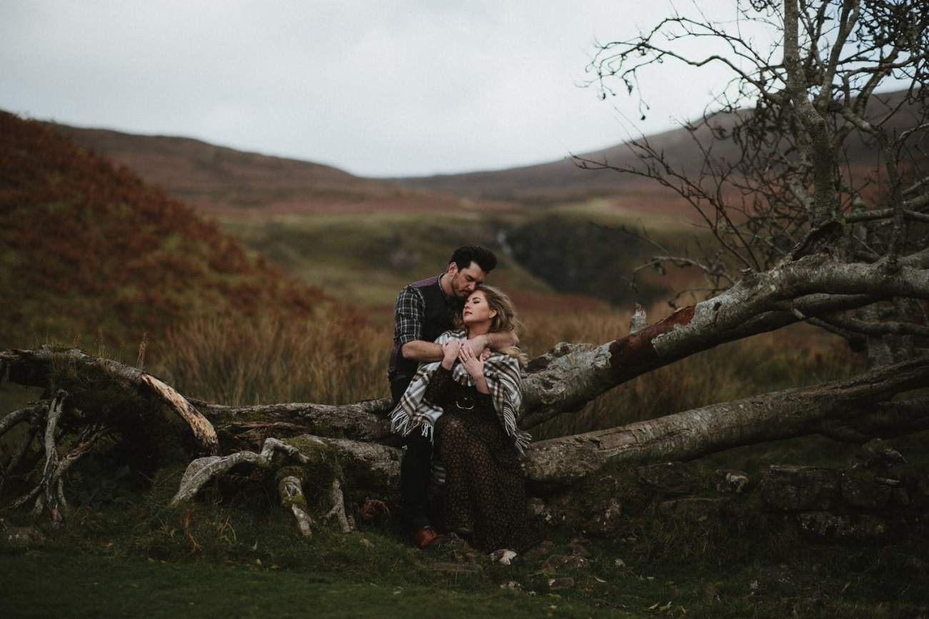 Couple sitting together on a fallen tree during their Isle of Skye anniversary session