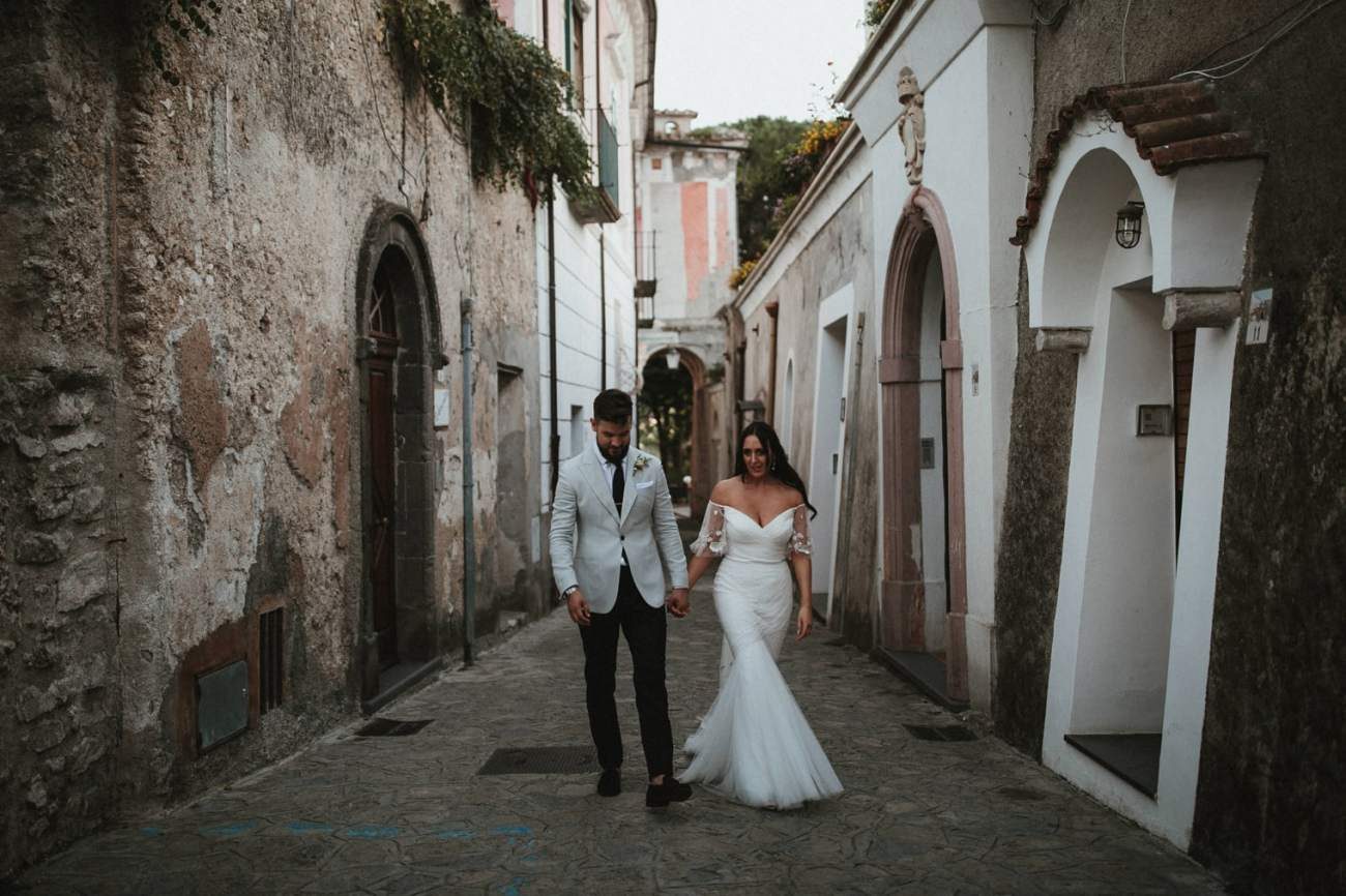 Couple walking hand in hand in the streets of Ravello during their Italian wedding