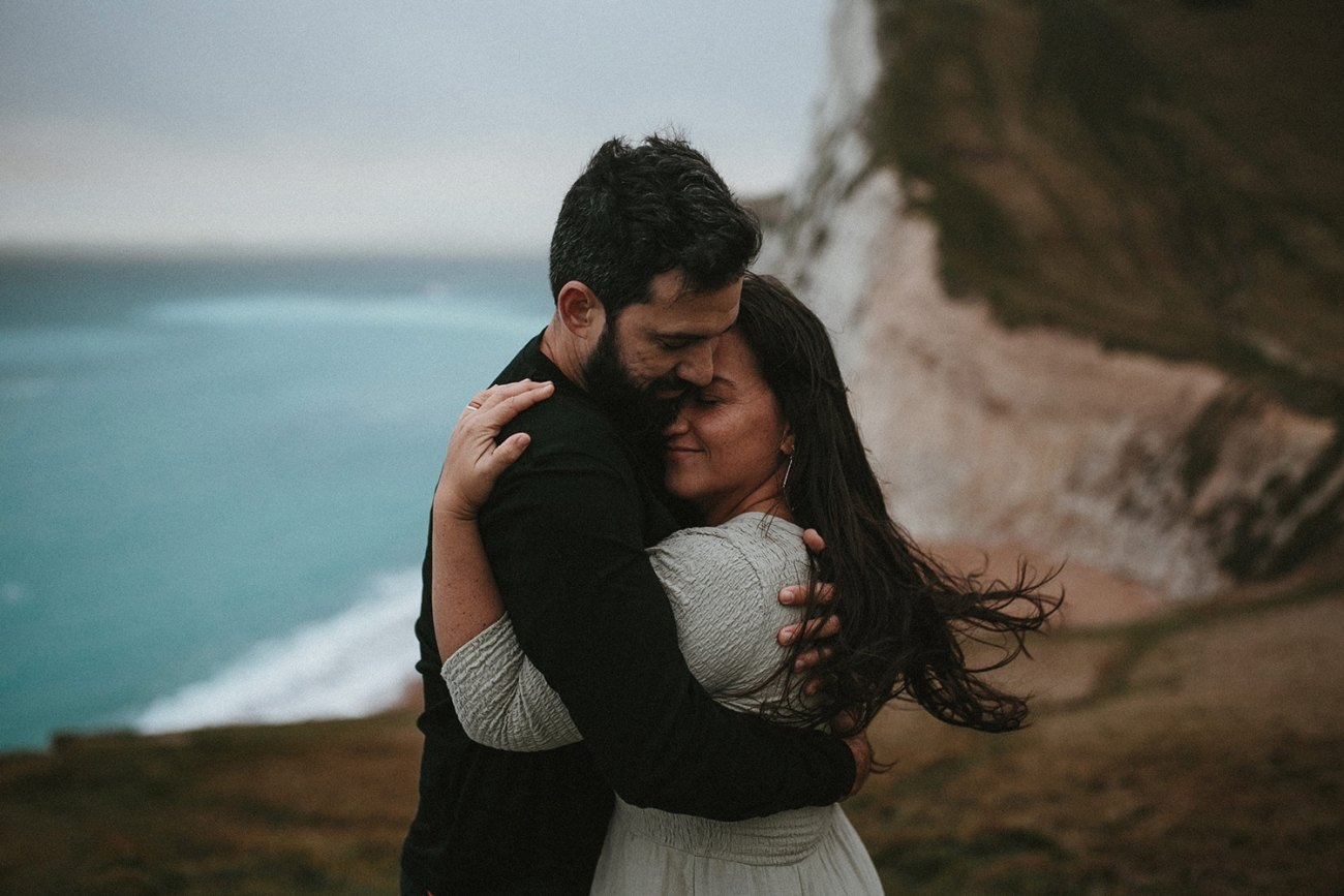 Couple holding each other during durdle door engagement session