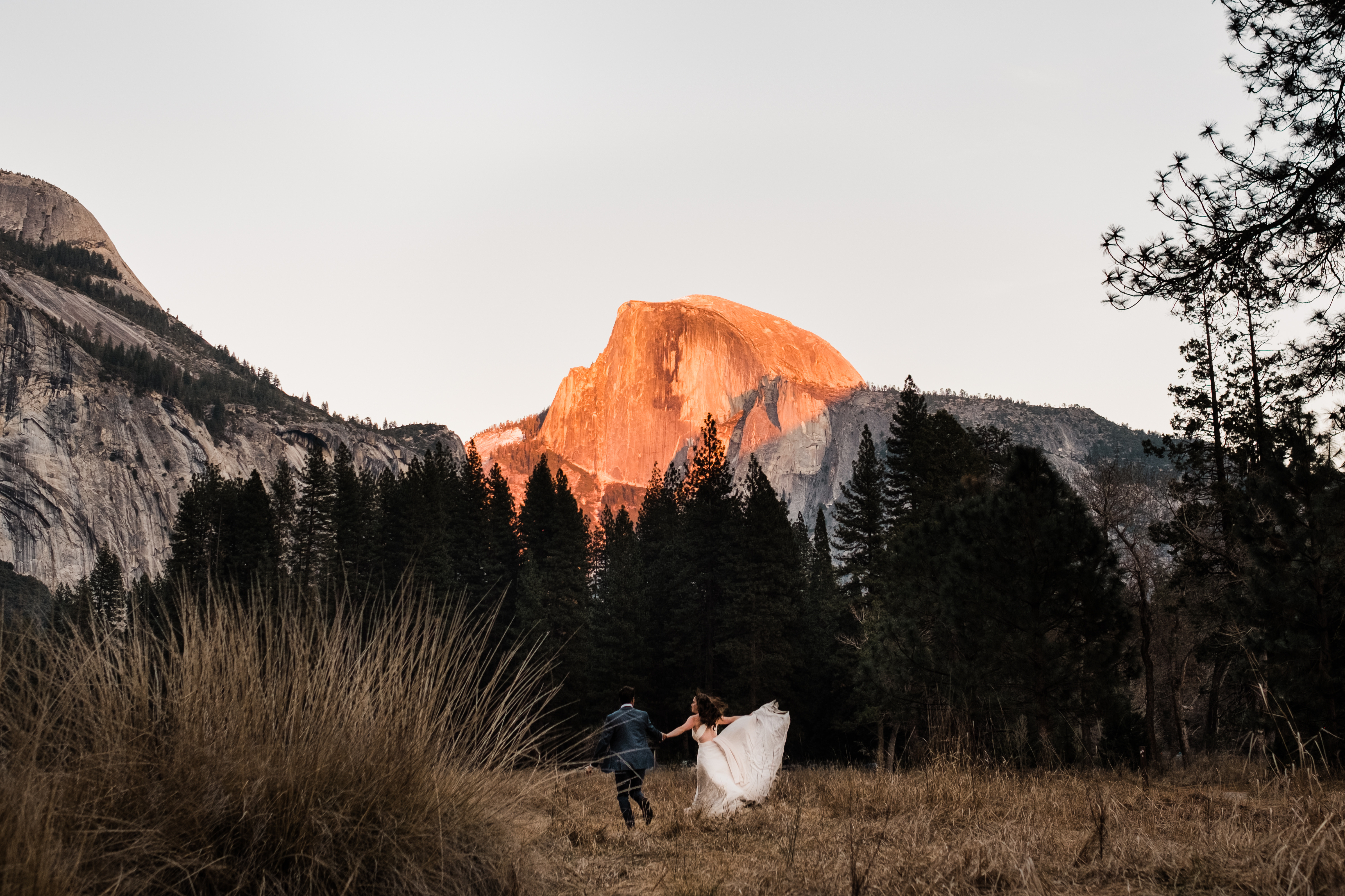 Half Dome gleams with fiery sunlight as the sun sets on Ryan and Kim's adventure elopement session in the Yosemite Valley.