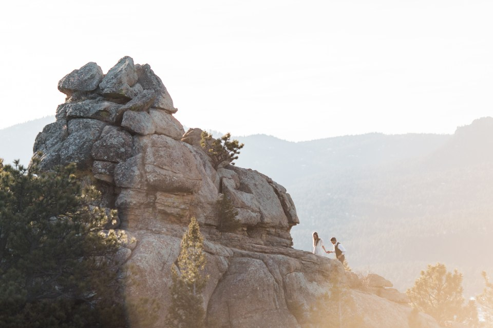 Anne and Caleb scrambled up a rock outcropping at the foothills of Colorado's Rockies at sunrise for their adventure elopement.