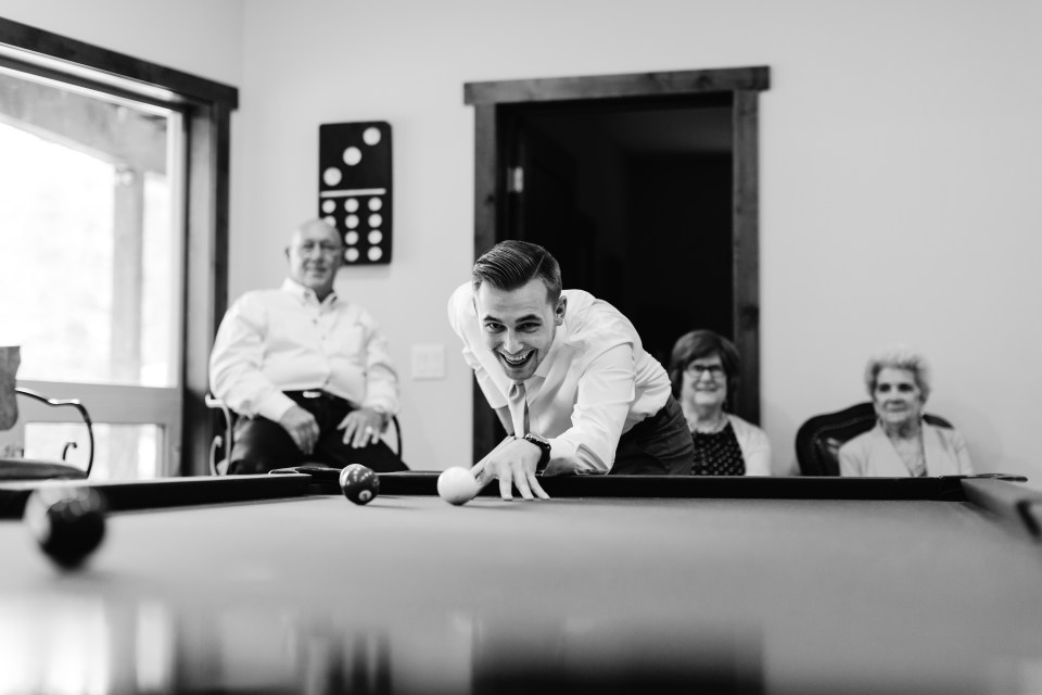 Blayke nervously strikes the cue ball in his pre-wedding game of pool with all his groomsmen and family watching.