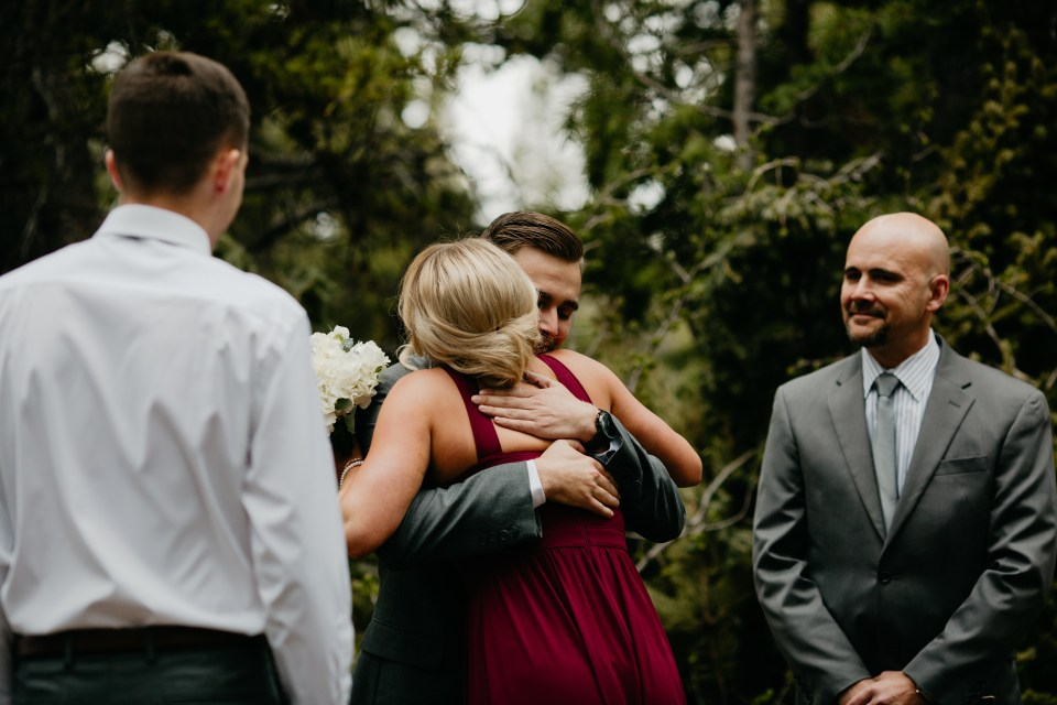 The bride's sister embraces her new brother-in-law as she makes her way to the other bridesmaids.