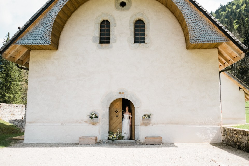 The Old World meets the New as this elopement bride stands in a 17th century church in the French Alps.