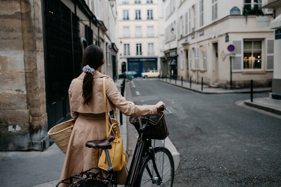 Eleanora leads her cruiser bike home from her neighborhood market on a rainy Sunday morning in April in Paris.