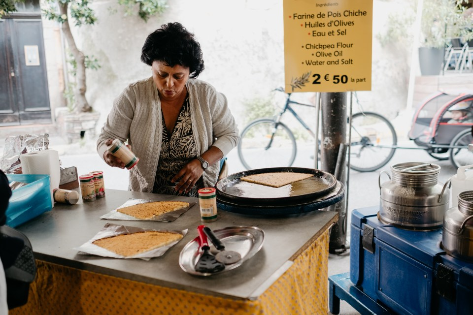 A woman prepares delicious crepe-style snacks in the Provencal market in Antibes.