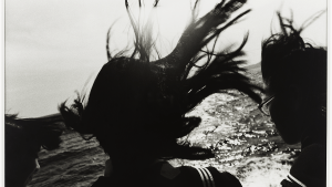 black and white photo of three individuals facing the ocean, hair blowing in the wind