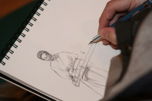 Close up of a sketch pad and hand with pencil.