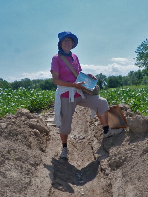 Claudia Chang stands astride an irrigation ditch.