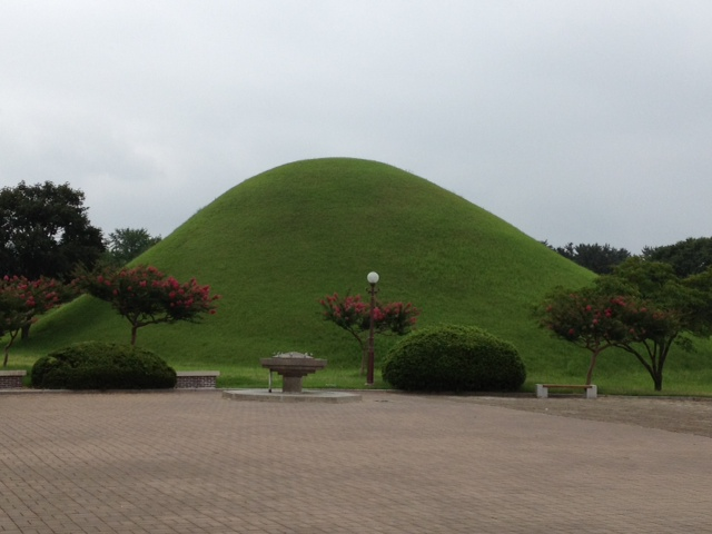 Large mound covered in grass with flowering trees at the base.