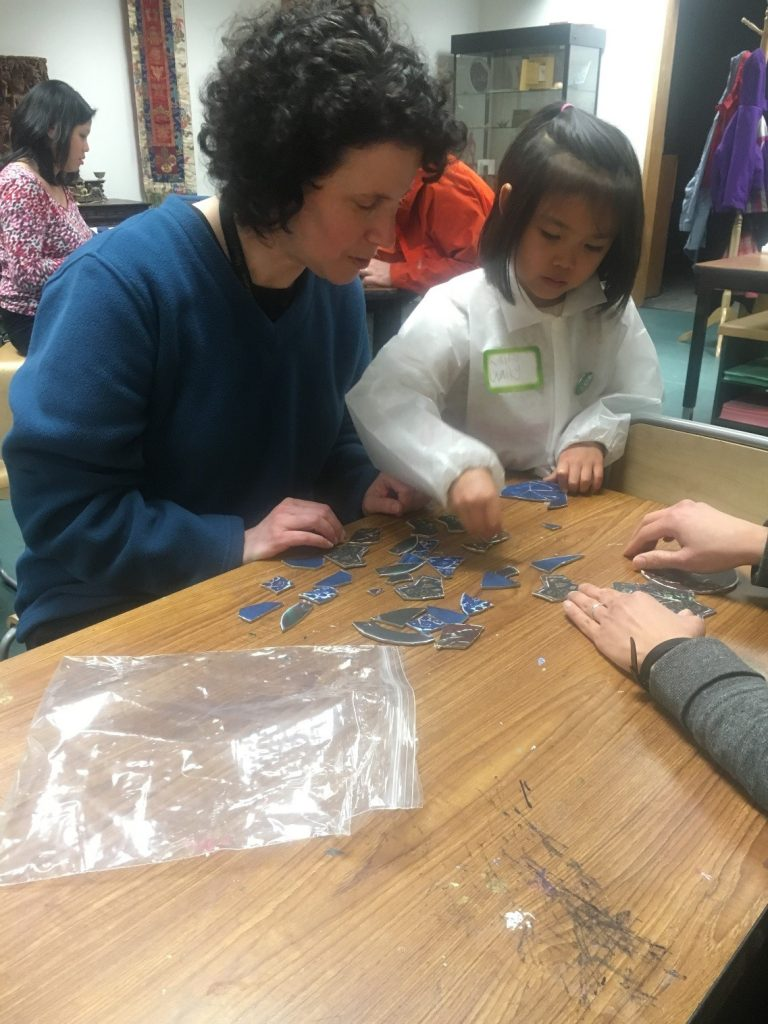 """Conservator Ellen Chase works with program participants on reassembling their """"ceramic"""" puzzlesduring the first Art and Me workshop."""