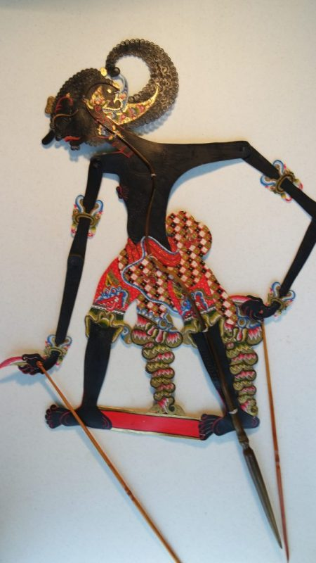 Cut-out puppet with long, thin arms controlled by sticks, with intricately patterned clothing.