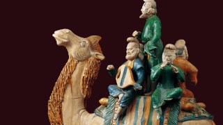 Colorful sculpture of three musicians riding a camel