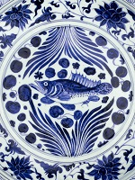 Detail of a blue and white ceramic dish painted with a fish in the center.
