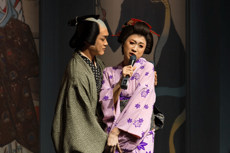 Actor portraying Utamaro holds the actress portraying Okita Naniwaya