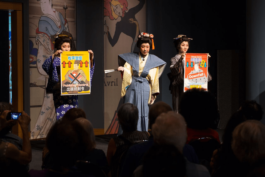 Two actresses hold posters, while another actor speaks
