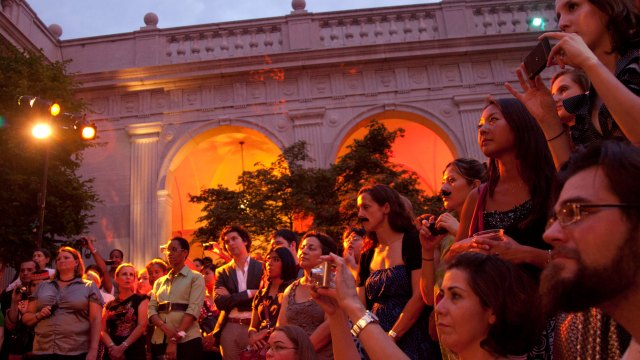 Partygoers fixated on an unseen spectacle in a warmly lit Freer courtyard.