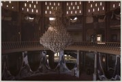 The interior of an abandoned building, with a grand by dilapidated chandelier.