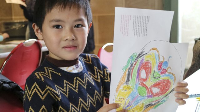 child holds up drawing