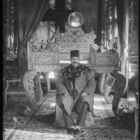 Nasir al-Din Shah sitting on the lower step of the Sun Throne