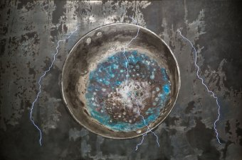 A round metal container on a distressed metal background, faint purple lightning scrawling over the foreground