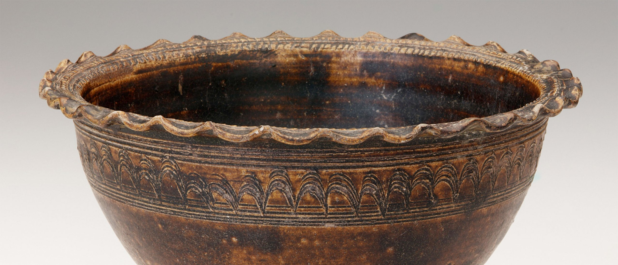 detail of a pedestal footed bowl. A brown bowl with a wavy lip and an inscribed band with a wavy center