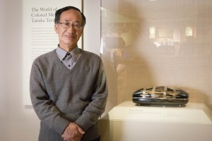 Clad in a grey sweater and button up, hands clasped and gently smiling, the artist poses next to his piece Dreamy Movement, a rectangular box decorated with broad silver bands and gold and silver ovals.