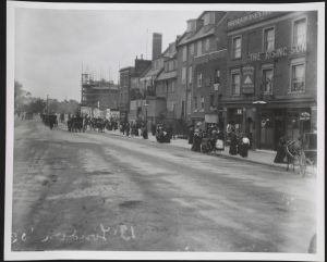 Black and white photo of street with procession on right.