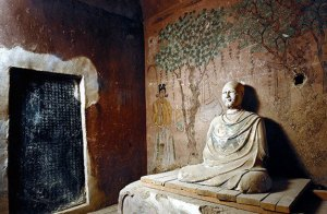 A buddha sculpture seated in a room with a panting behind