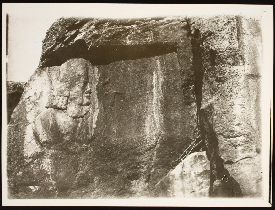 The face of High Priest Kartir, with hand raised and outstretched, in relief on rock face.