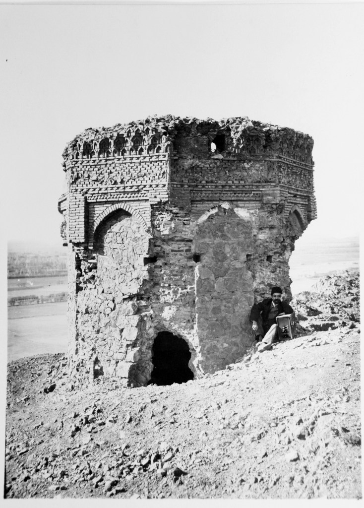 A stone tower with crumbling archways juts up from the rocky ground, a small irregular entrance to the tower contrasts with the light-colored stone. A man rests against the tower in its shade.