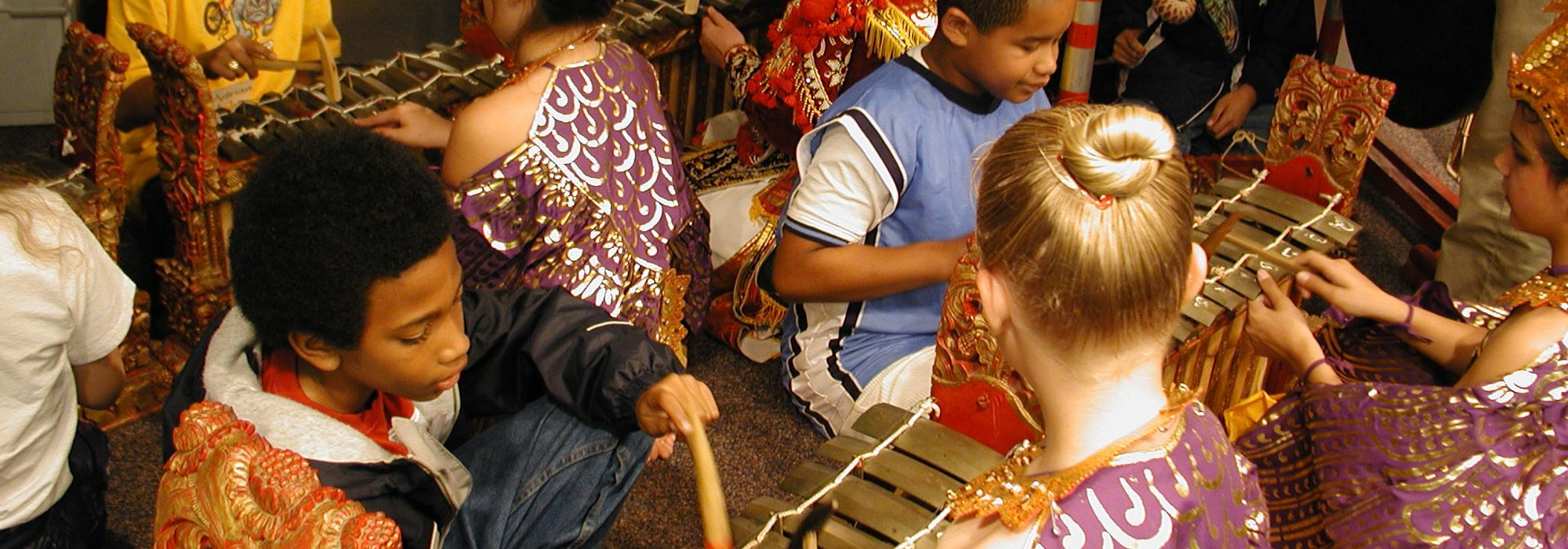 Children playing ugal in a gamelan class.