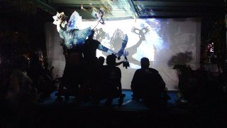 Puppeteers and dancers casting silhouettes onto the backside of a screen.
