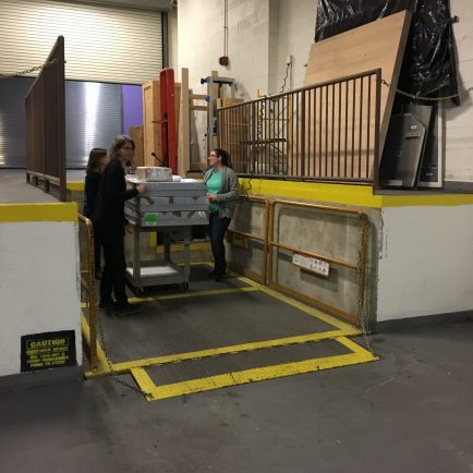 three staff members taking a cart of wrapped boxes on a loading dock lift