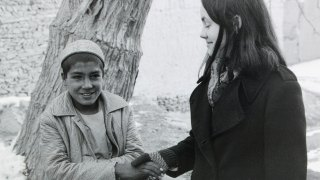 Maura shaking hands with village boy