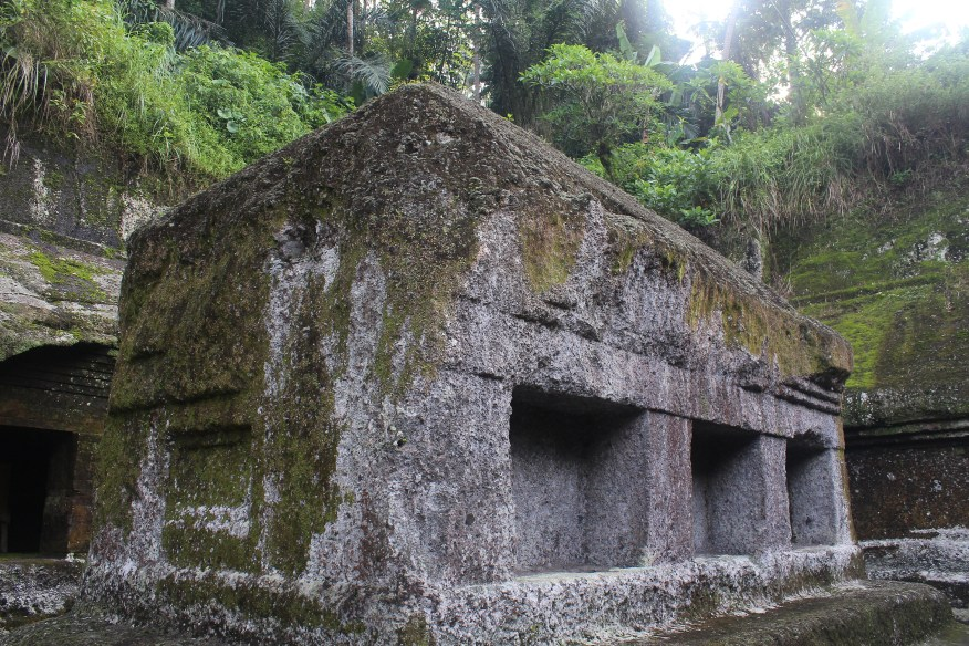 Rock-cut shrine, partially ruined, with caves