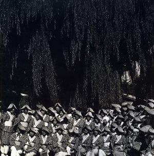 black and photo of large group of people all wearing same ceremonial garb with hats