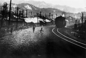 a photograph of train tracks, mountains and powerlines in the distance