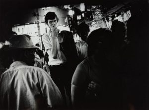 A black and white photo in which figure stands looking at other figures