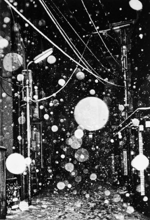 a black and white image, floating white globes among powerlines