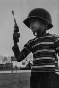 A black and white photo of a child holding a gun, wearing a helmet and a striped shirt